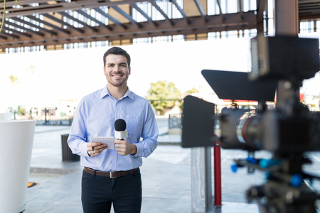 Portrait of handsome smiling newsman holding microphone and notepad in front of camera Stock Photo