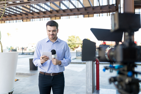Confident male interviewer reading news in front of camera outdoors