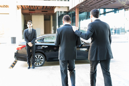 Dedicated security agent providing protection to popular celebrity while walking towards car Stock Photo