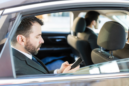 Side view of mid adult CEO using mobile phone while traveling with bodyguards in car
