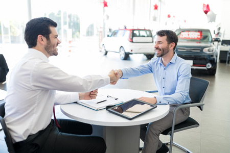Mid adult seller and buyer smiling and looking at each other while shaking hands at car dealership 写真素材