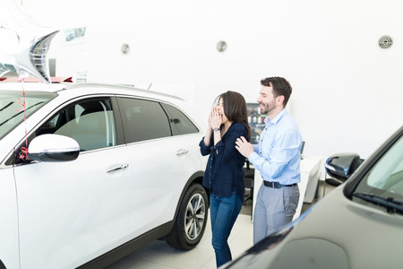 Mid adult man surprising woman with new car on her birthday in car dealership salon