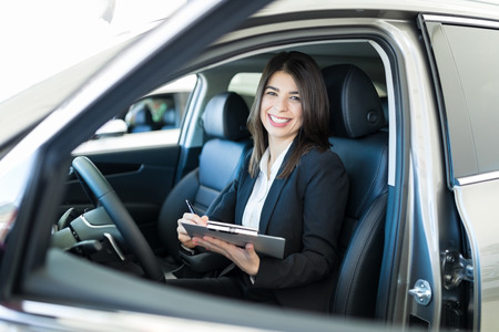 Good looking sales representative writing on clipboard while sitting in new luxury car