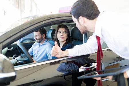 Beautiful customer understanding specifications of car by creative salesman at dealership 版權商用圖片