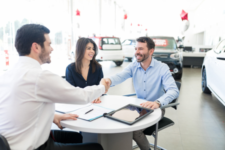 Mid adult representative giving good wishes to couple on purchase of car in showroom Imagens