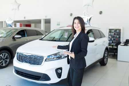 Mid adult seller showing the best car as per budget in dealership