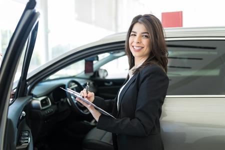 Brunette saleswoman writing specification of car interior at salon 版權商用圖片