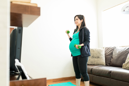 Confident pregnant woman lifting dumbbells to stay healthy at home