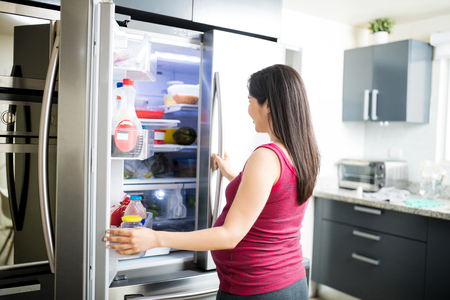 Hispanic expectant mother searching healthy food in fridge at home