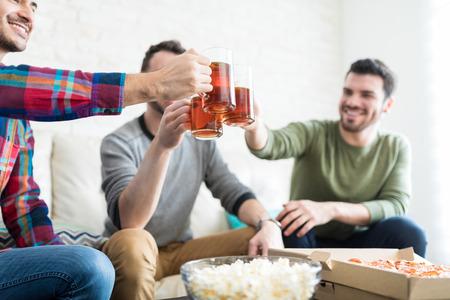 Male buddies raising beer mugs while enjoying weekend party in living room Stock Photo