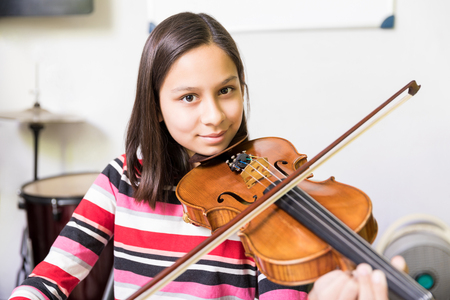Little skillful student getting violin training as a part of extracurricular activities in school
