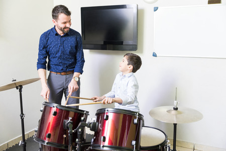 Smiling music teacher educating boy with his drum playing techniques