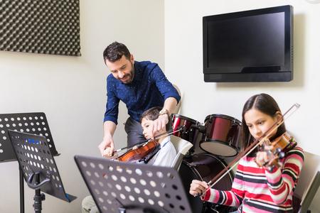 Mitte erwachsener Mann, der Jungen beim Geigenspiel im Musikunterricht unterstützt