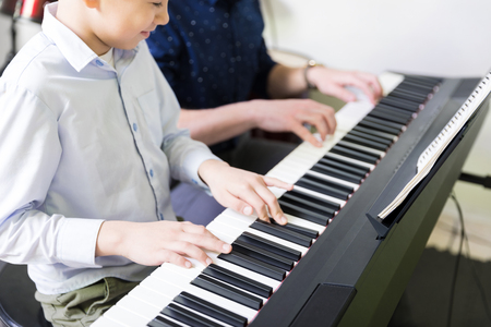 Midsection of boy learning to play electric piano from teacher in music class