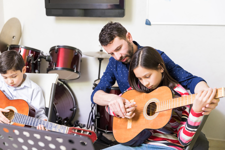 Caring teacher positioning fingers of teen girl on guitar in music school