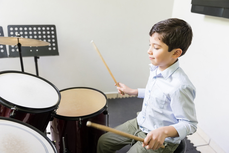 Caucasian boy learning to play drum in music class Banco de Imagens