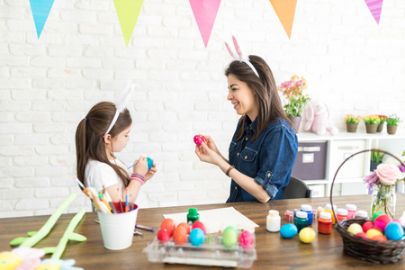 Family wearing bunny ears while preparing for Easter holiday at home