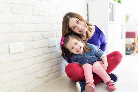 Cheerful mother and daughter wearing casuals while sitting near wall at home Banco de Imagens