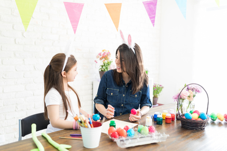 Elementary girl looking at mother painting Easter eggs during spring season Stock Photo