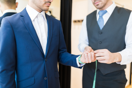 Midsection of creative young seamster measuring wrist of wealthy man in clothing store