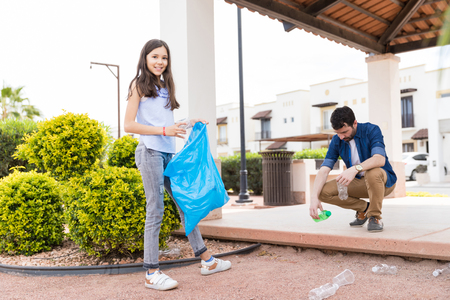 Happy preteen girl with father collecting recyclable plastic bottles in garden