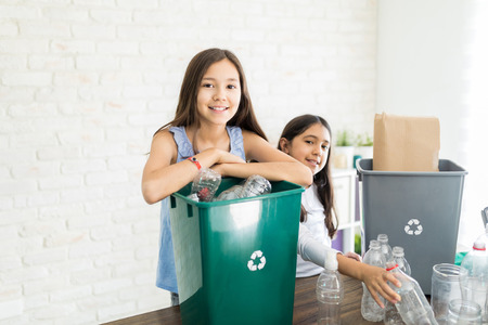 Portrait of confident preteen girl gathering bottles with sister at home