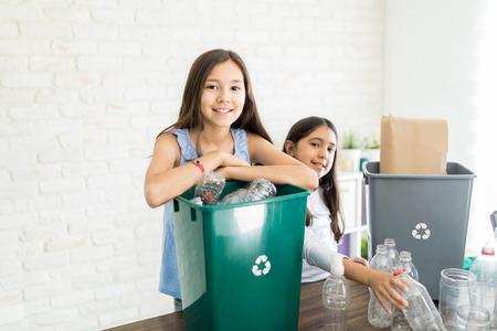 Ritratto di fiduciosa ragazza preadolescente che raccoglie bottiglie con la sorella a casa