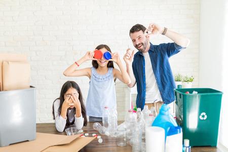 Family making fake eyeglasses with lids while enjoying recycling activity