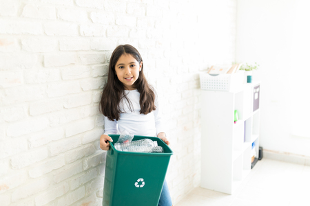 Innocent and responsible girl making an eye contact while recycling plastic at home