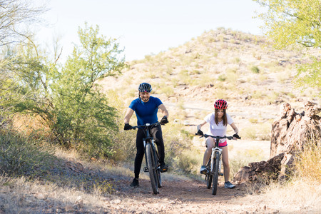 Mountain bikers taking efforts to ride bicycles on rough trail Imagens