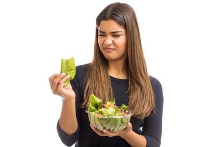 Frau, die im Studio ein starkes Gefühl der Abneigung gegen grünes Gemüse zeigt