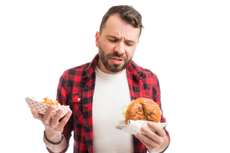 Mid adult man holding burger and fries and making a face on white background