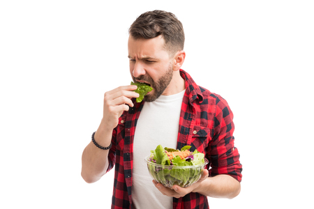 Disgusted mid adult man eating lettuce from bowl in studio Imagens