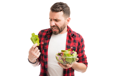 Man looking at lettuce with disgust with a desire to avoid dieting Imagens