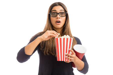Scared pretty lady having popcorn while wearing 3D glasses on white background