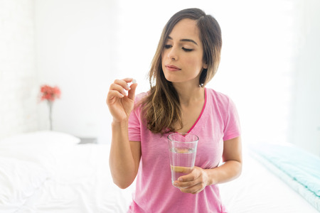 Sick mid adult woman taking dose of medicine while sitting on bed