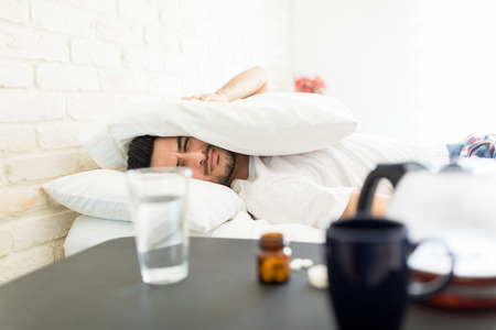 Frustrated man covering head with pillow making unpleasant face while lying in bedroom