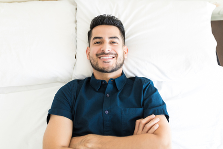 Confident handsome guy with arms crossed in bed