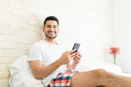 Portrait of attractive man installing new app on smartphone in bedroom Stockfoto