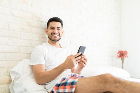 Portrait of attractive man installing new app on smartphone in bedroom Archivio Fotografico