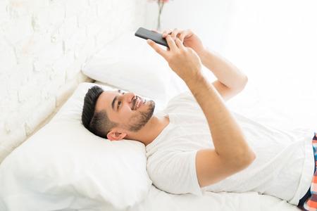 Smiling good looking man watching funny videos on smartphone in bed Zdjęcie Seryjne