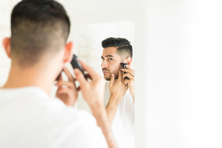 Attractive Hispanic man shaving with electric trimmer near mirror at home
