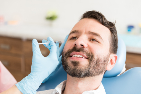 Closeup of mid adult man smiling while undergoing anti-aging treatment Stock Photo