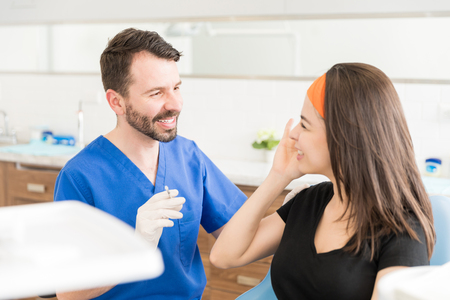 Dermatologic cosmetic surgeon and patient smiling in medical esthetic office