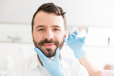 Smiling man taking treatment to smooth out unwanted wrinkles to keep looking and feeling younger