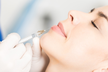 Closeup of fillers are pushed in dermal layer of woman's lip to enhance shape at skincare clinic