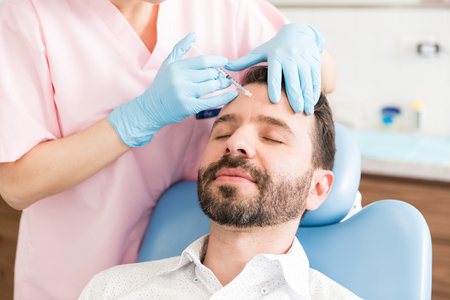 Calm male patient receiving wrinkle smoothing injection by surgeon in clinic Stock Photo