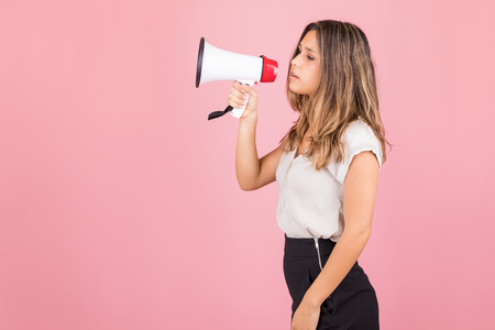 Young woman making some important announcement using megaphone over pink background