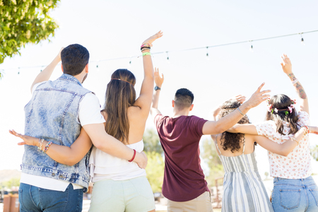 Rear view of best friends dancing together with arm around in music festival during summer