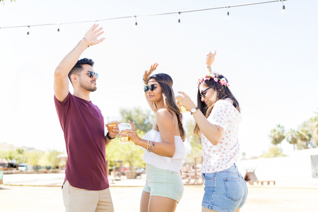 Carefree best friends dancing with arms raised at music festival Stok Fotoğraf